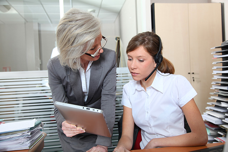 A business woman shows an intern wearing a headset something on her tablet.
